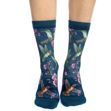 These fun socks feature images of the ruby-throated hummingbird flying and sitting on branches, with pink flowers around then on a background of floral patterned blue. The sole, toe, heel, and rim are the same blue, without the floral patterns. The active fit socks sport elastic arch bands to contour to your feet and provide support.