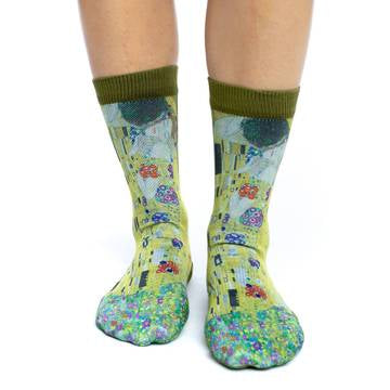 "These fun socks feature a print of the famous painting ""The Kiss"" by Gustav Klimt. The painting is of a man kissing a woman on the cheek on a field of flowers. The heel and rim of the socks are the same olive green as the background of the painting. The active fit socks sport elastic arch bands to contour to your feet and provide support."