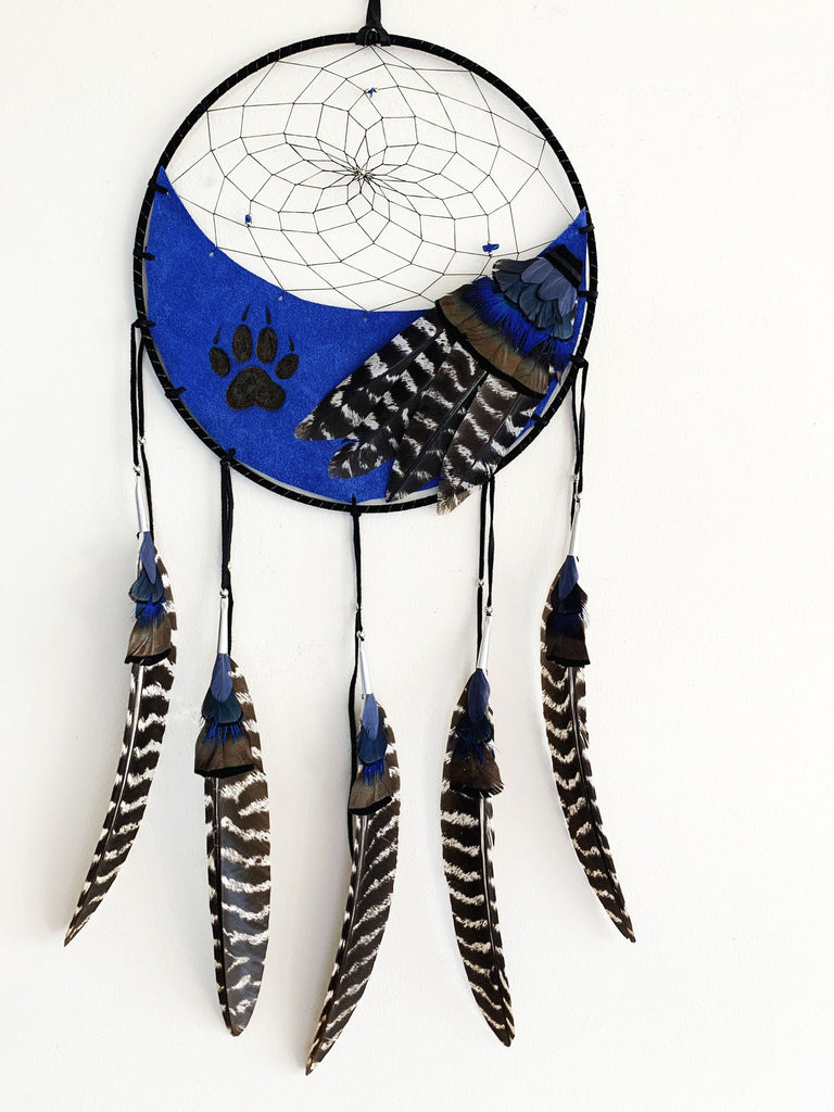 This dream catcher features a crescent of blue leather with a wolf's paw print branded onto it. Above the leather, string is woven in a spiral pattern with small rocks and beads threaded into it. Blue, and white and black feathers lay across the leather on the right, and hang from five leather strings along the bottom.