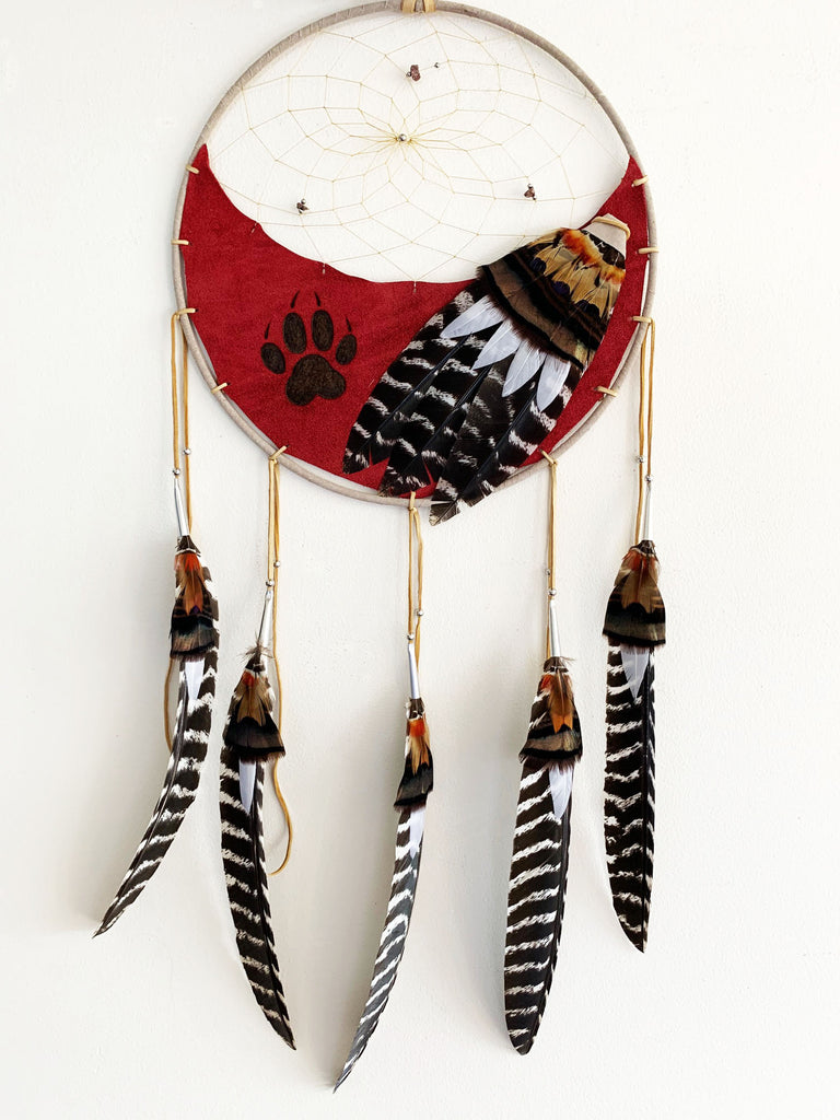 This dream catcher features a crescent of red leather with a wolf's paw print branded onto it. Above the leather, string is woven in a spiral pattern with small rocks and beads threaded into it. Brown, and white and black feathers lay across the leather on the right, and hang from five leather strings along the bottom.