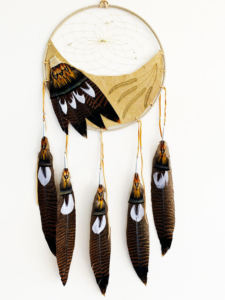 This dream catcher features a crescent of tan leather with grain stalks branded onto it. Above the leather, string is woven in a spiral pattern with small rocks and beads threaded into it. White, and brown and black speckled feathers lay across the leather on the left, and hang from five leather strings along the bottom.