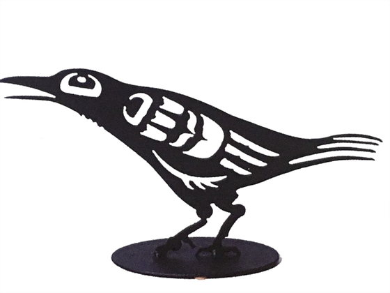 This metal sculpture shows the matte black silhouette of a baby crow drawn in Coastal Salish style. It is leaning forward with its beak slightly open. The slim tail, beak, and feather forms on this crow give it a dainty appearance.