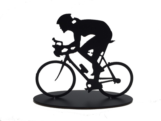 This metal sculpture shows the matte black silhouette a female cyclist hunched forward over their handle bars. She faces left and stares forward intently. The bike design is slightly simplified, and the wheels have no spokes. The piece stands on an oval base.