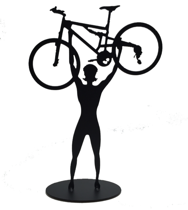 This metal sculpture shows the matte black silhouette a female cyclist facing the viewer. She holds a mountain bike triumphantly above her head. The bike design is slightly simplified, and the wheels have no spokes. The piece stands on a small oval base.