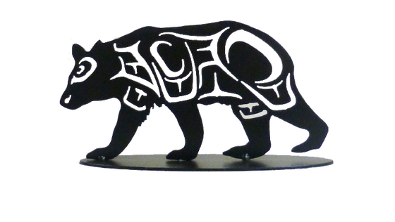 This metal sculpture shows the matte black silhouette of a hummingbird drawn in Coastal Salish style. The bear is mid stride, moving right to left. Coastal Salish shapes make the details of the bear's broad legs and head.