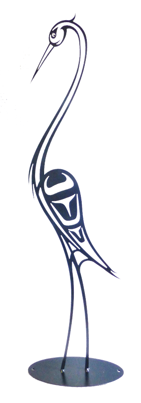 This metal sculpture shows the matte black silhouette of a heron drawn in Coastal Salish style. The heron stands tall with its beak pointing downward. Coastal Salish forms provide the details of its face and wings. It's long neck and slender legs curve gracefully. The sculpture sits on a circular metal base.