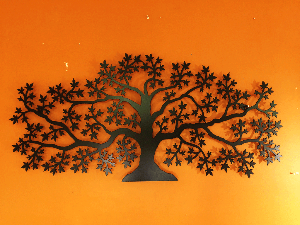 A matte black wall mounted maple tree on an orange wall.