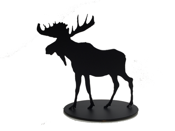 This metal sculpture shows the matte black silhouette of a moose. It has a full rack of antlers and a pronounced dewlap. Its strong shoulders contrast with its slender legs. Careful detailing along the edges give this piece a strong sense of realism. It stands on an oval base.