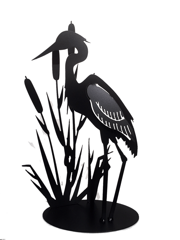 This metal sculpture shows the matte black silhouette of a heron standing with cattails. The wing of the heron has been partially punched out of the metal, and bent to render the bird in 3D. Individual wing feathers are visible. The cattails are cut very delicately and in lifelike shape and proportion to the heron. The piece sits on an oval base.