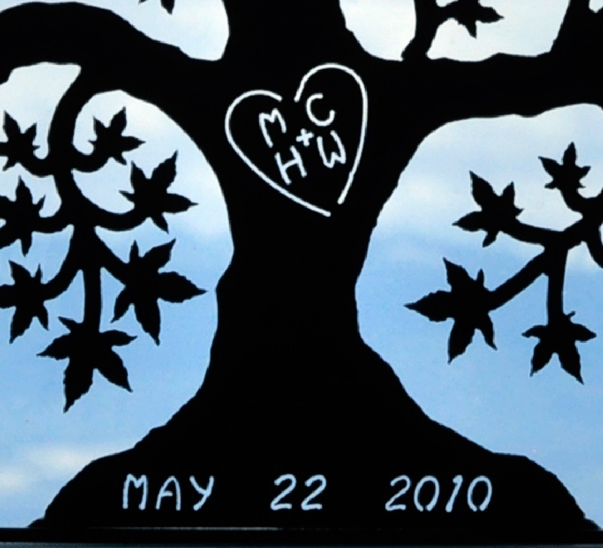 "A close up of a matte black tree of love. The initials ""MC + HW"" are carved into the trunk, enclosed by a heart. The date ""May 22, 2010"" is carved into the base. This photo highlights the contrast between the matte black sculpture and the bright light passing through the carving."