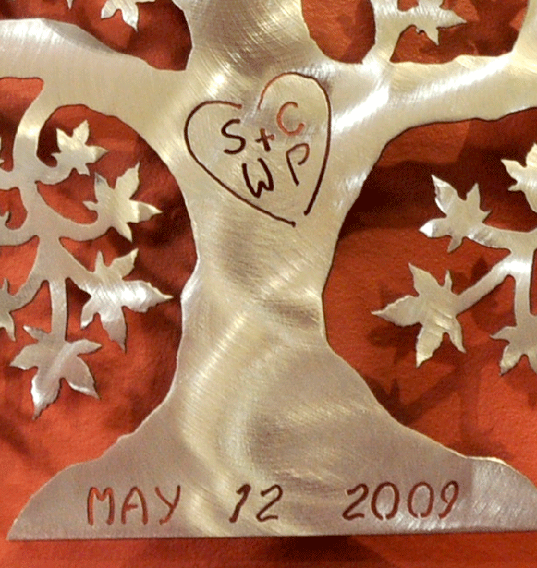 "A close up of a brushed metal tree of love on a brown wall. The initials ""SC + WP"" are carved into the trunk, enclosed by a heart. The date ""May 12, 2009"" is carved into the base. Although more subtle, the brushed metal tree still contrasts significantly with the darker background, allowing good legibility of the text."