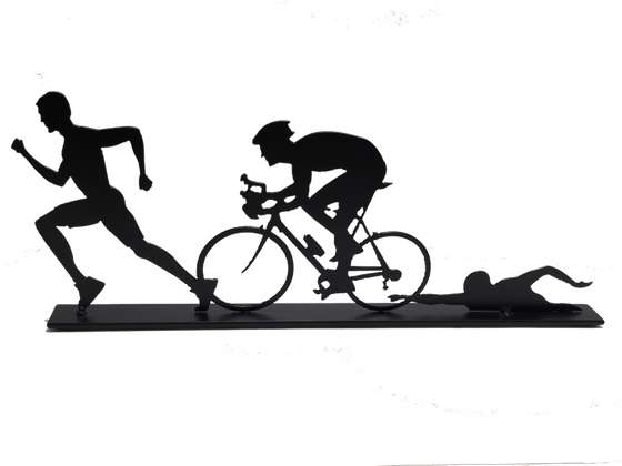 This metal sculpture shows the matte black silhouette of three male figures, each doing one trial in a triathlon. The leftmost is running, the center is biking, and the rightmost is swimming. The silhouettes slightly overlap each other. This piece sits on a narrow rectangular base.