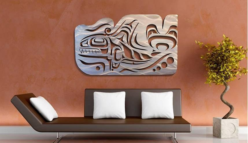 A Coastal Salish Orca wall sculpture hung on a wall. The large sculpture is two thirds as long as the couch beneath it.