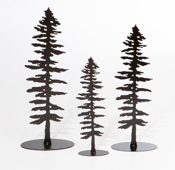 Three metal sculptures each show the matte black silhouette of a Sitka pine tree.  The designs of each tree are identical, but each sculpture is a different size, with the largest on the left and the smallest in the center. The Sitka tree is tall but slim. Its short, broad branches are about the same length along the whole tree, except at the top where they form a point. The sculpture sits on an oval base.