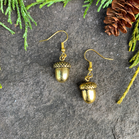 Two small gold acorn charms sit on a stone background. A gold earring hook is attached to the top of each acorn.