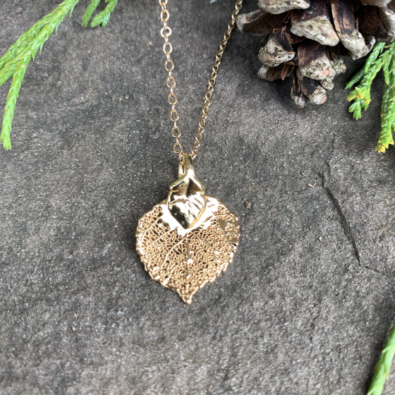 A small gold coated aspen leaf on a gold chain sits on a stone background. The gold has a bright finish. At the top of the picture are decorative evergreen leaves and a pine cone.