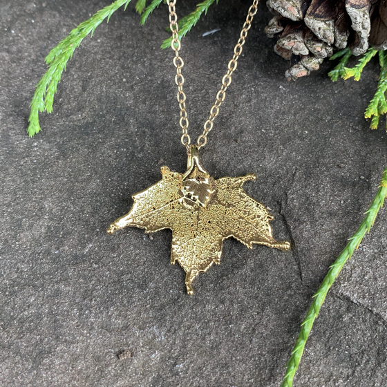 A small gold coated maple leaf on a gold chain sits on a stone background. The gold has a bright finish. At the top of the picture are decorative evergreen leaves and a pine cone.