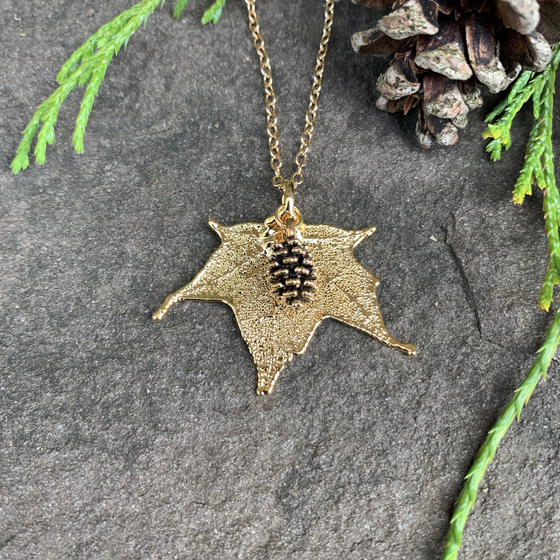 A small gold coated maple leaf on a gold chain sits on a stone background. Attached to the maple leaf is a tiny gold pinecone. The gold has a bright finish. At the top of the picture are decorative evergreen leaves and a pine cone.
