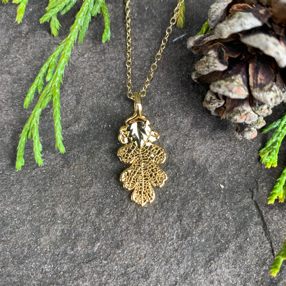 A small gold coated oak leaf on a gold chain sits on a stone background. The gold has a bright finish. Around the picture are decorative evergreen leaves and a pine cone.