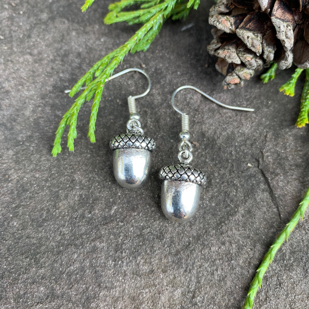 Two small silver acorn charms sit on a stone background. A silver earring hook is attached to the top of each acorn.