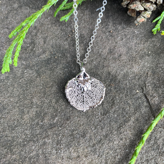 A small silver coated aspen leaf on a silver chain sits on a stone background. The silver has a bright finish. At the top of the picture are decorative evergreen leaves and a pine cone.