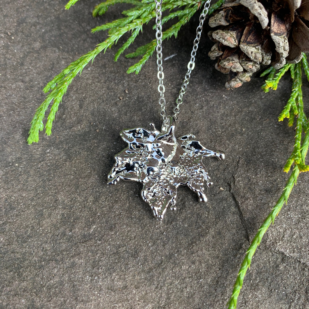 A small silver coated maple leaf on a silver chain sits on a stone background. The silver has a bright finish. At the top of the picture are decorative evergreen leaves and a pine cone.