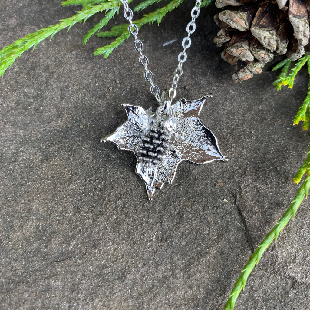A small silver coated maple leaf on a silver chain sits on a stone background. Attached to the maple leaf is a tiny silver pinecone. The silver has a bright finish. At the top of the picture are decorative evergreen leaves and a pine cone.