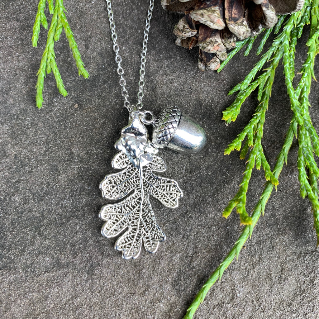 A small silver coated oak leaf on a silver chain sits on a stone background.  Also attached to the chain is a small silver acorn charm. The silver has a bright finish. Around the picture are decorative evergreen leaves and a pine cone.
