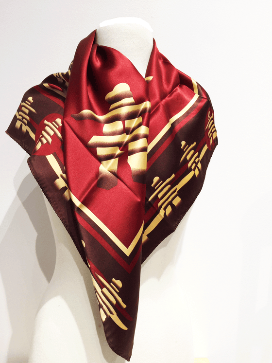 Pictured here is a burgundy silk scarf with yellow and brown accents. Featured on the scarf is the stately Canadian Inukshuk.