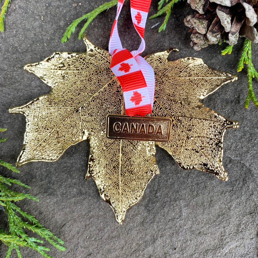 "A large gold coated maple leaf sits on a stone background. A ribbon patterned with Canadian flags is tied to the stem end of the leaf. On the ribbon is a small gold charm that says ""Canada"". The gold has a bright finish. Around the picture are decorative evergreen leaves and a pine cone."