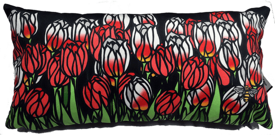 This large pillow features a field of tulips. There are a mix of red tulips and Canada 150 tulips, which are white with fiery red-yellow streaks. The leaves and stems are bright green. The bold line art give the tulips a stained glass appearance.  At the bottom right of the pillow is the artists mark—a small picture of a bee.