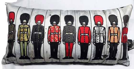 This large pillow features nine soldiers in ceremonial outfits. Each soldier wears long pants, a belted jacket, and a tall beefeater hat. Each jacket has a unique colourful print on it—for example, polka dots, flowers, stripes or sheet music. At the bottom right of the pillow is the artists mark—a small picture of a bee.