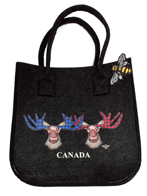 This small dark grey felt bag has two overhead handles and features an art print of two moose. The left moose's antlers are coloured with blue buffalo check, while the right moose has red buffalo check. The moose's ear, nose, face and neck are all coloured with different shades of brown. Underneath the moose the word Canada has been written in white text. At the bottom right of the picture is the artists mark—a small picture of a bee.