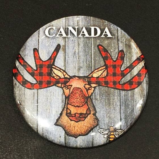This magnet features an art print of a moose. The moose's ear, nose, face and neck are all coloured with different shades of brown. Its antlers are coloured with red buffalo plaid. Above the moose the word Canada is written in white text. At the bottom right of the picture is the artists mark—a small picture of a bee.