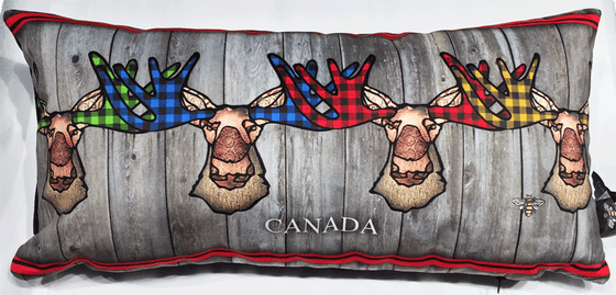 This large pillow features four funky moose. The moose's ear, nose, face and neck are all coloured with different shades of brown. Each moose's antlers are coloured with either green, blue, red, or yellow buffalo check. A decorative red stripe runs along the top and bottom of the pillow. Underneath the moose the word Canada has been written in white text. At the bottom right of the pillow is the artists mark—a small picture of a bee.