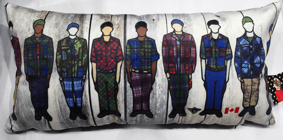 This large pillow features eight soldiers standing at attention. Each soldier is wearing long pants and a jacket with a unique colourful tartan print.  At the bottom right of the pillow is the artists mark—a small picture of a bee.