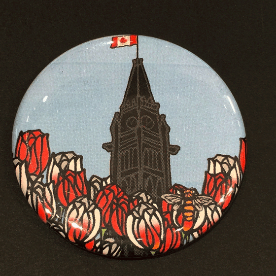 This magnet features an art print of the peace tower and a field of tulips. The peace tower is in the center of the picture and is flying the Canadian flag. The field of flowers has red tulips and Canada 150 tulips, which are white with fiery streaks of red. At the bottom right of the picture is the artists mark—a small picture of a bee.