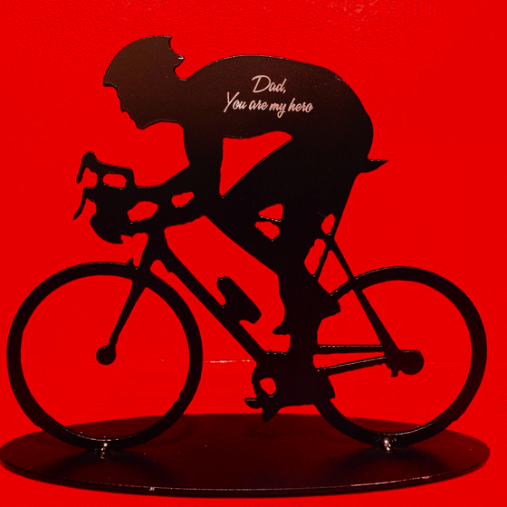 "A metal sculpture of a male cyclist. The sculpture has been painted matte black. Direct engraving of the words ""Dad, You are my hero"" onto cyclist's back makes the silver of the underlying metal shine against the black paint."