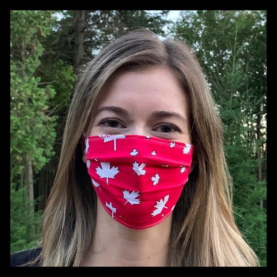 "A female model wearing a red face mask featuring white maple leaves and the word ""Canada."" Two elastic ear bands are included for easy wearability."