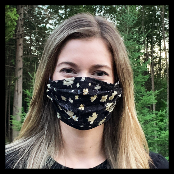 "Black face mask featuring cream coloured maple leaves and ""Canada."" Two elastic ear bands are included for easy wearability."