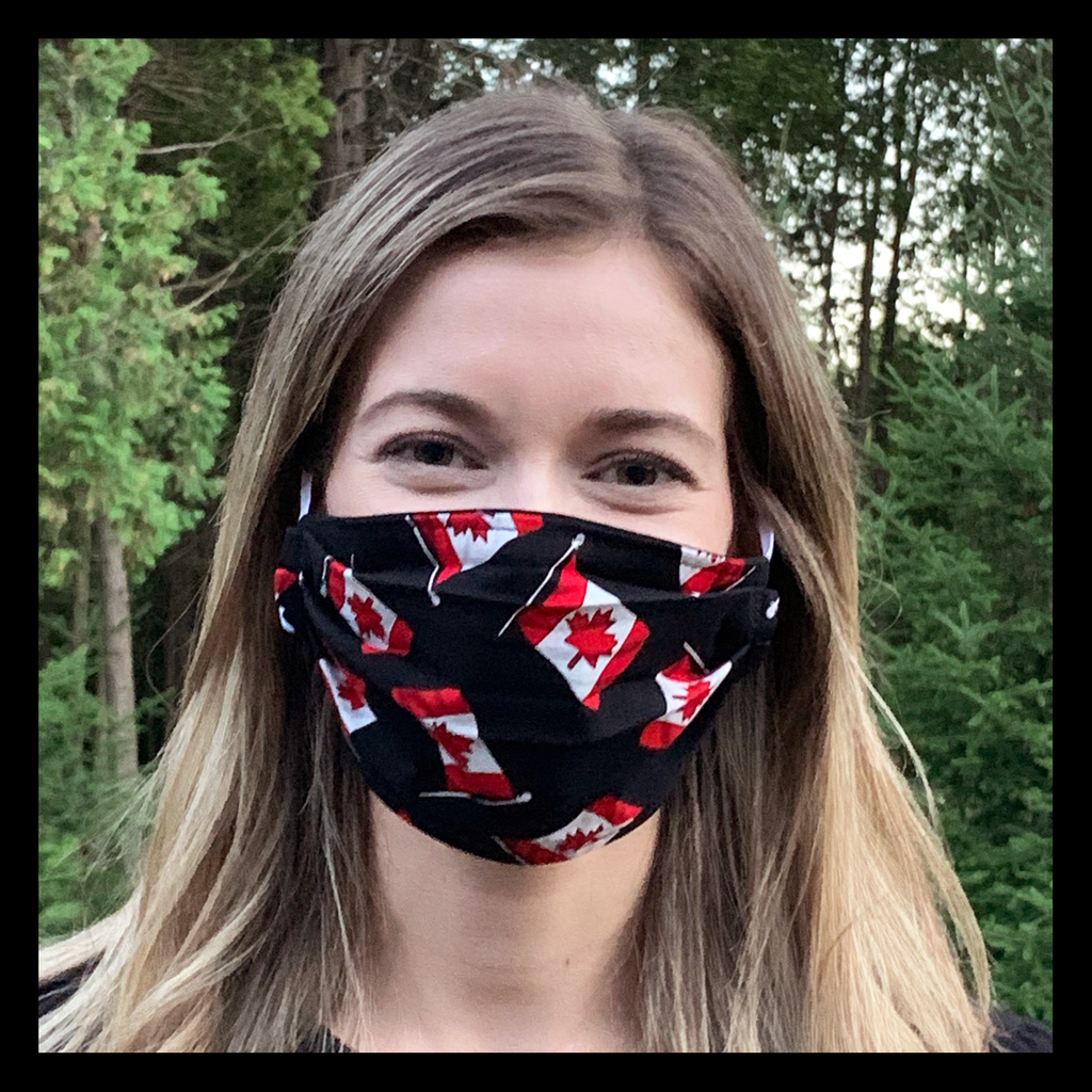 A female model wearing a black face mask featuring Canadian flags. Two elastic earbands are included for easy wearability.
