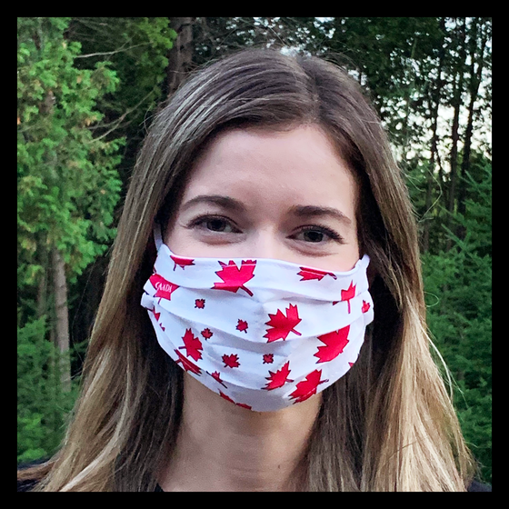 "A female model wearing a white face mask featuring red maple leaves and ""Canada."" Two elastic ear bands are included for easy wearability."