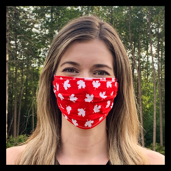 a female model wearing a red face mask featuring white maple leaves. Two elastic earbands are included for easy wearability.
