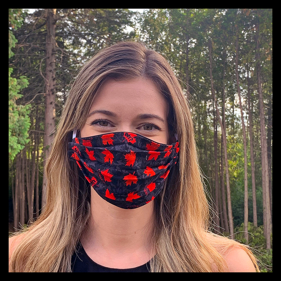 "A female model wearing a black face mask featuring red maple leaves and the words ""Canada"" and ""Eh"". Two elastic earbands are included for easy wearability."