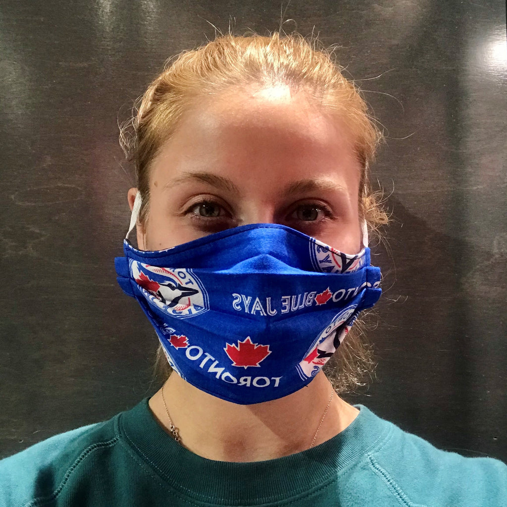 A female model wearing a blue face mask with a repeating pattern of the Toronto Blue Jays logo. Two elastic earbands are included for easy wearability.