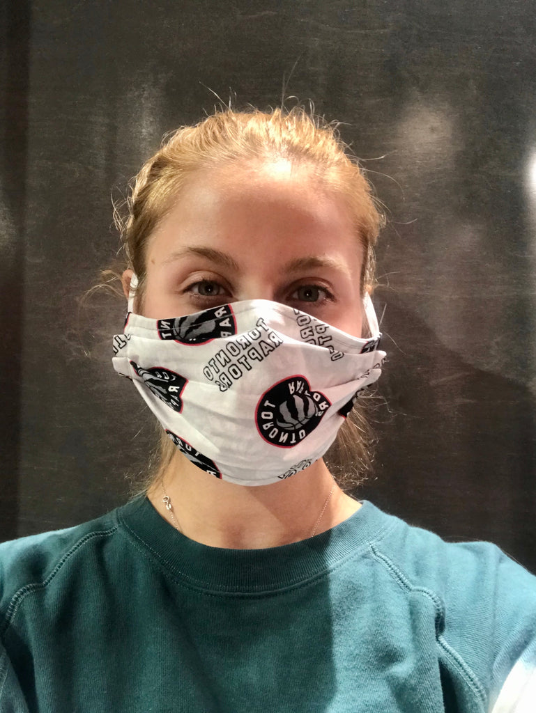 A female model wearing a grey face mask with a repeating pattern of the Toronto Raptors logo. Two elastic earbands are included for easy wearability.
