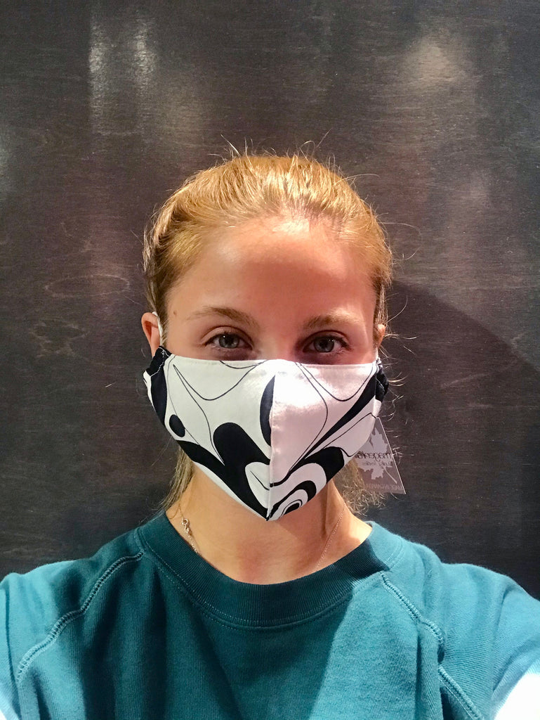 A female model wearing a black and white face mask with a partial design of a Nuxalt style raven. Two adjustable elastic earbands are included for easy wearability.