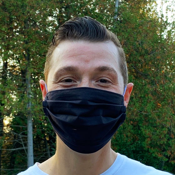 A male model wearing a solid black face mask. Two elastic earbands are included for easy wearability.