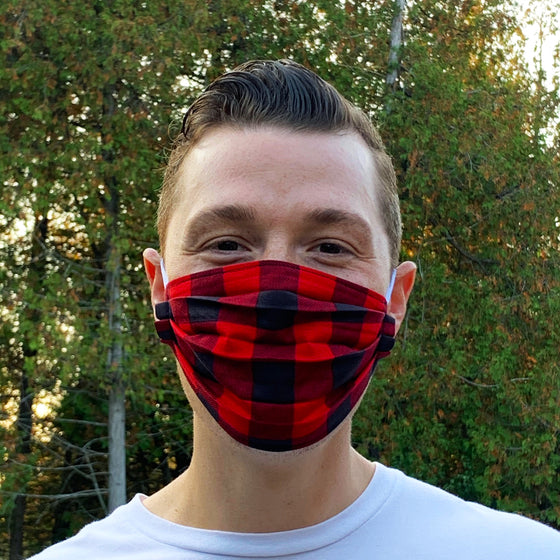 A male model wearing a buffalo plaid face mask. Two elastic ear bands are included for easy wearability.