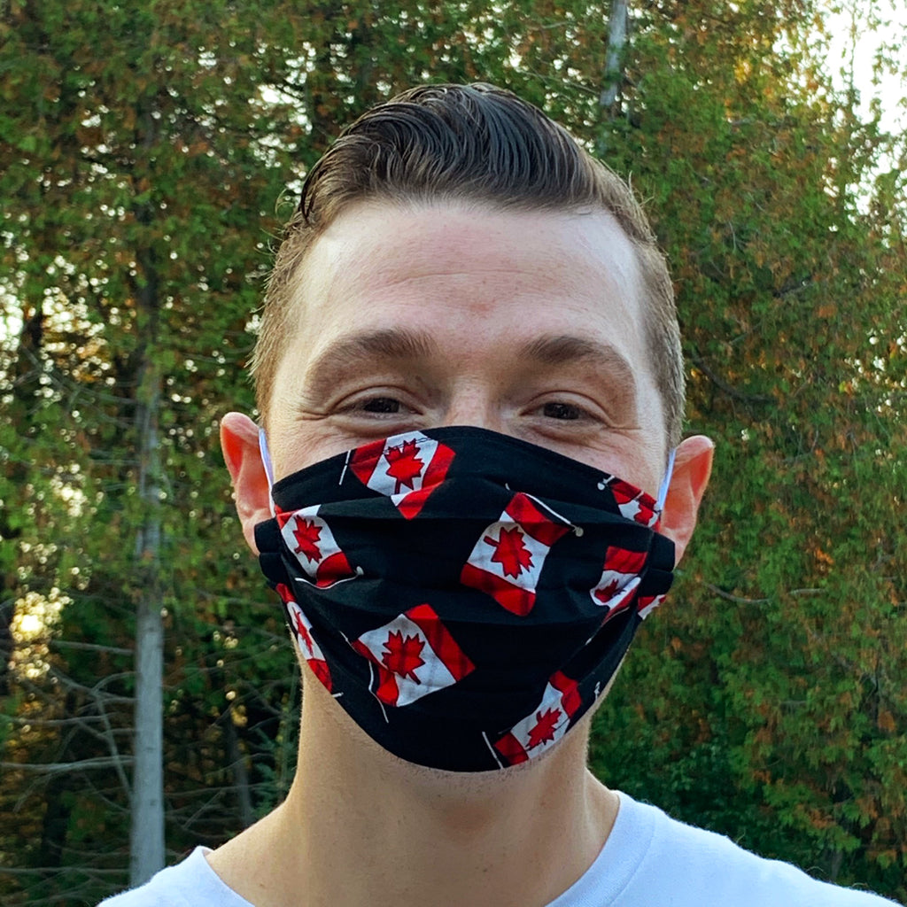 A male model wearing a black face mask featuring Canadian flags. Two elastic earbands are included for easy wearability.